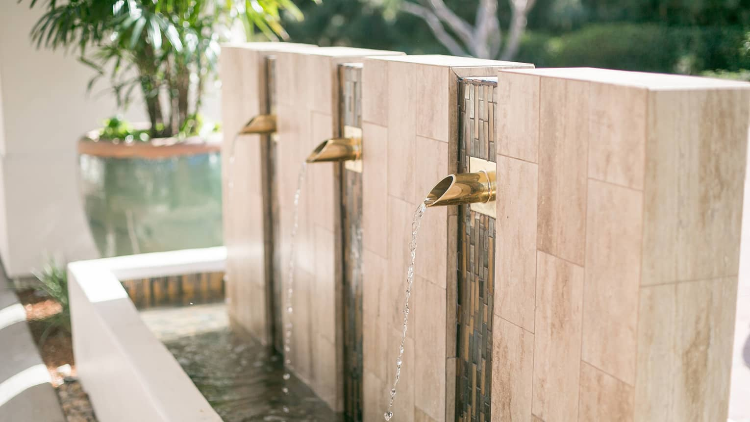Water falls from brass spouts of marble outdoor fountain