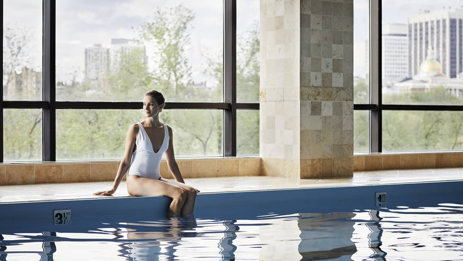 Woman in white swimsuit sits on edge of indoor swimming pool with legs in water