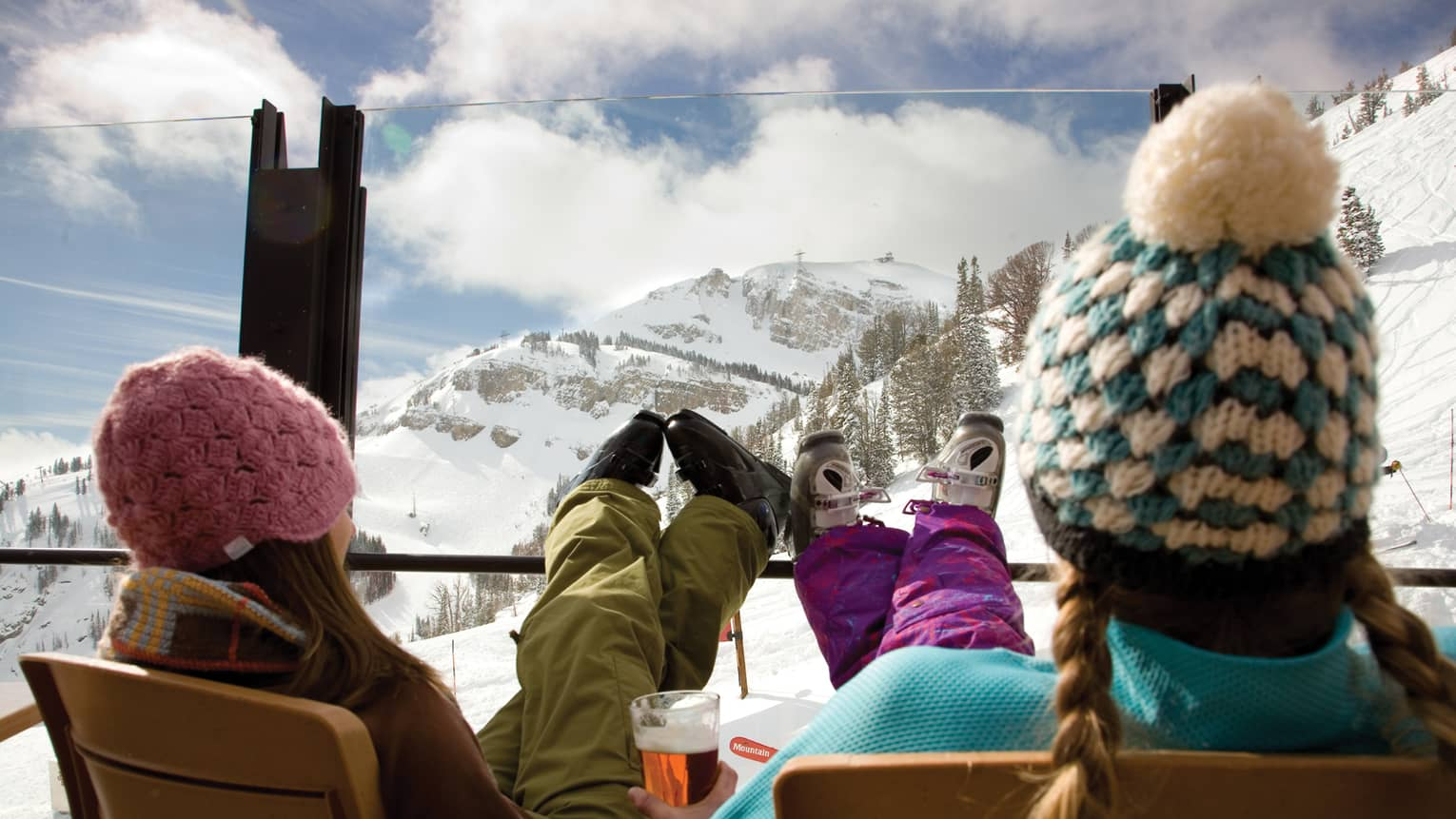 Two guests wearing hats and snow gear relax with their feet up near the ski slopes