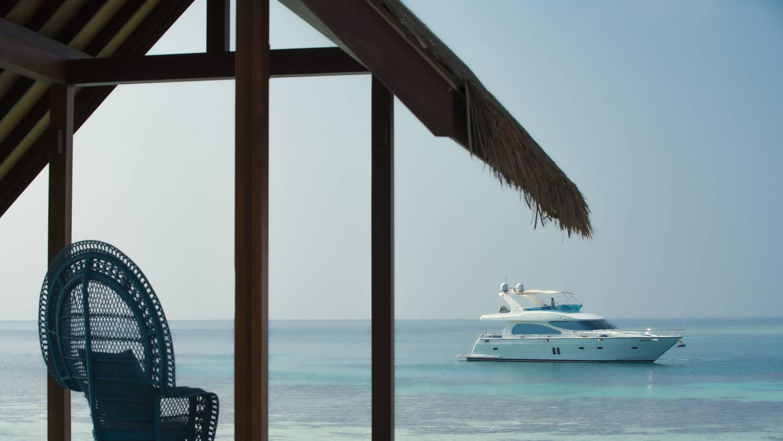 Wicker chair on cabana facing white private luxury yacht sailing on lagoon