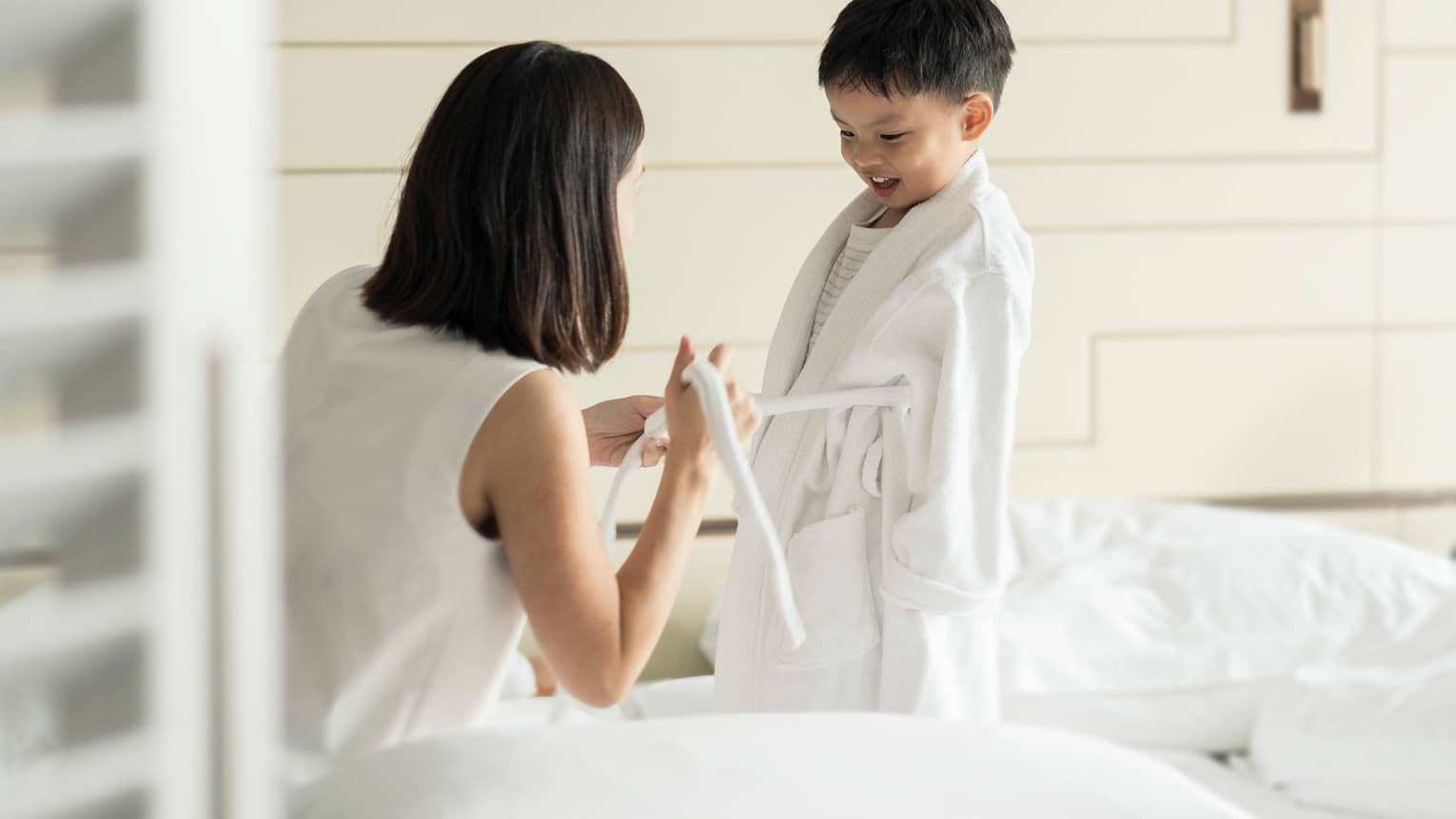 Woman kneels in front of young child, ties front of his white bathrobe