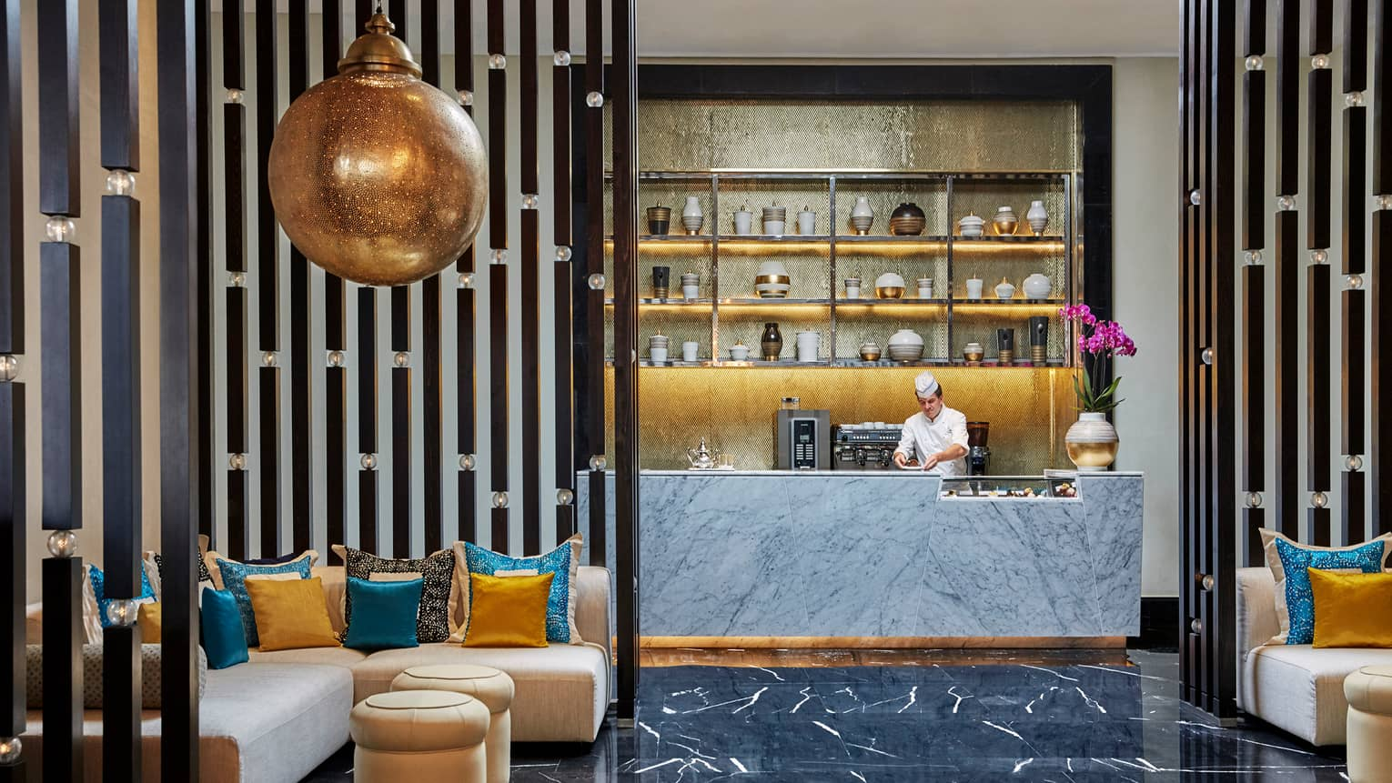 Chef behind counter, Mint lounge area with large brass hanging lamp, L-shaped sofas with colourful pillows, gilded accents
