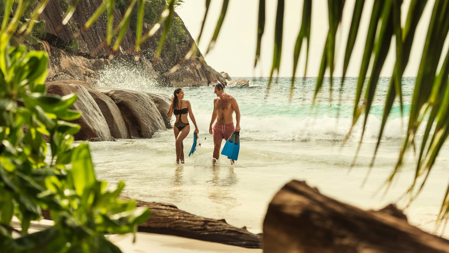Man and woman in swimsuits hold snorkelling fins, walk through tied up to beach