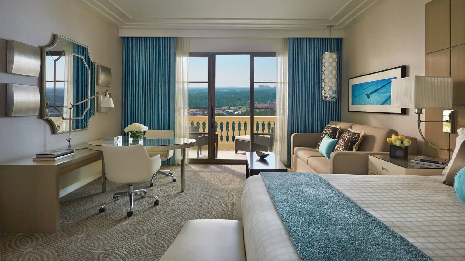 Golden Oak View Room bed with blue blanket, white chair at desk, sofa by balcony doors