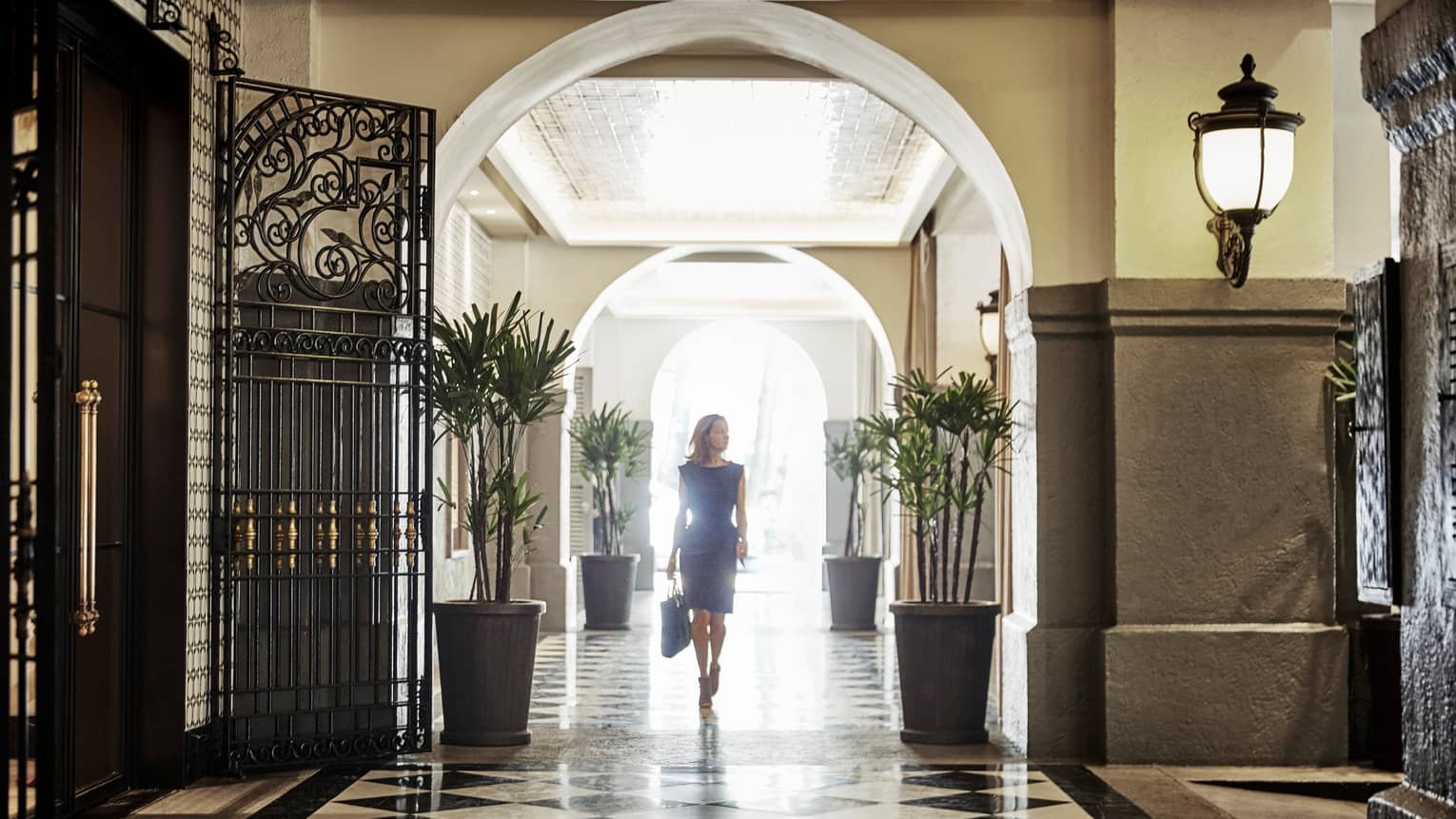Woman in blue dress walks down sunny marble hall past wrought-iron doors
