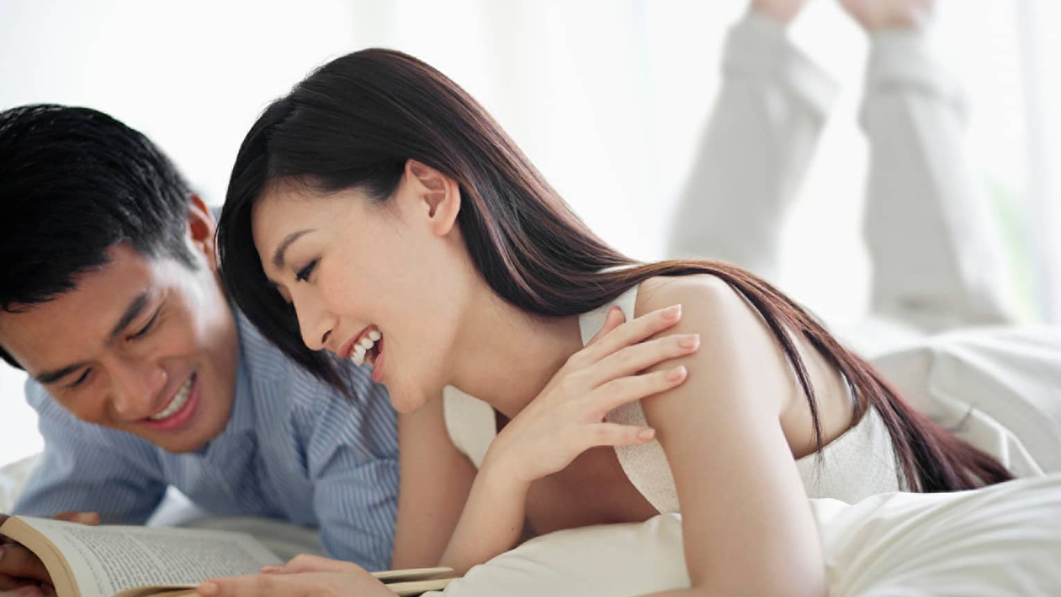 Smiling woman and man lounge on hotel bed, read book together