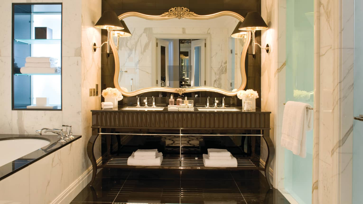 Large hotel bathroom vanity with double sink, tall mirror with gold frame, corner of marble bath visible
