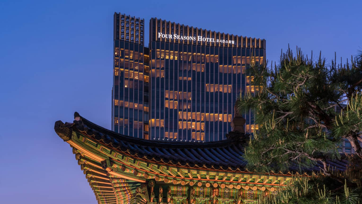 Four Seasons Hotel Seoul modern glass high rise with lights towering over traditional building at night