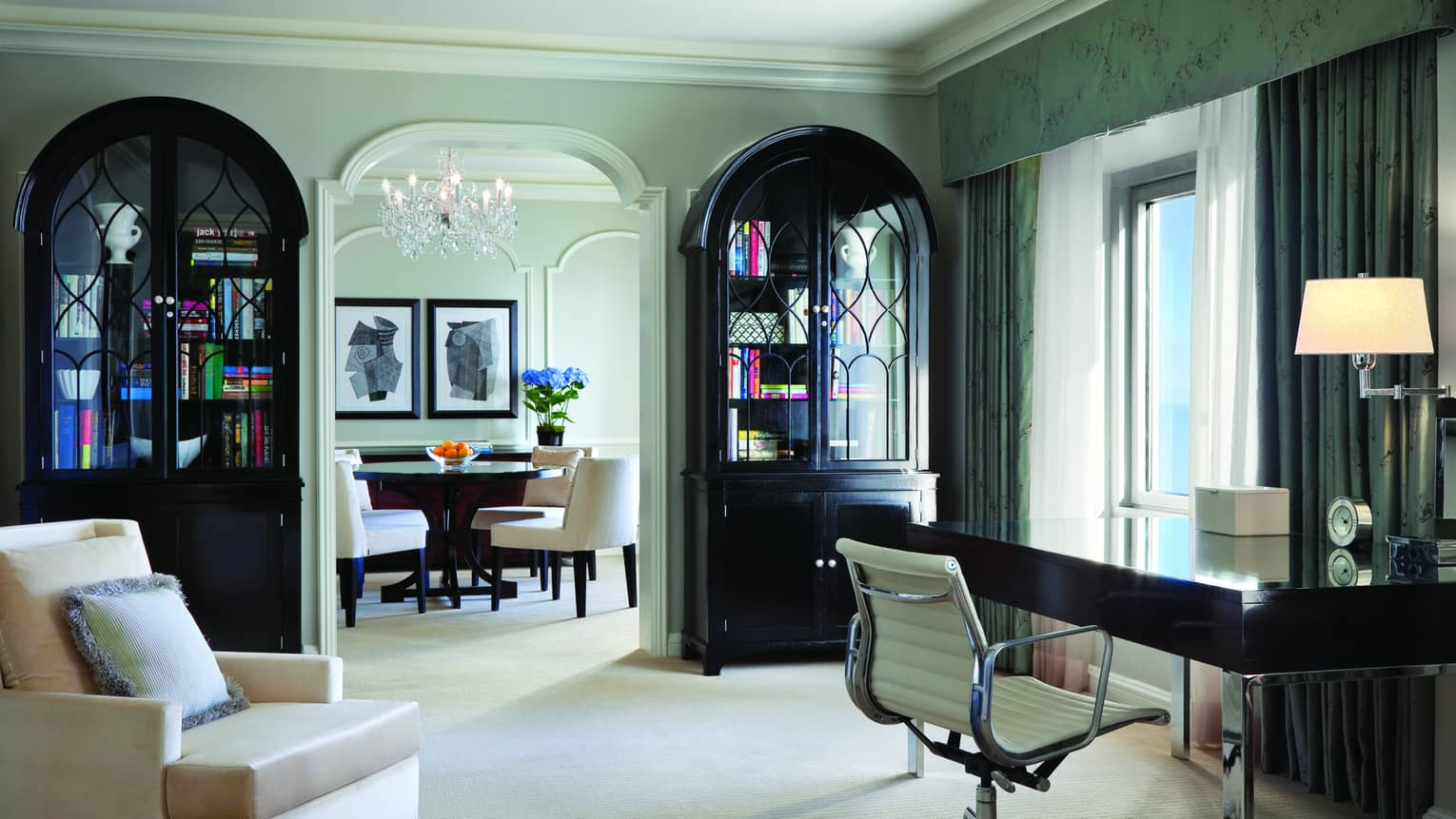 The 46th floor sunny Author Suite sitting room with two bookcases, writing desk and armchair, door to dining room