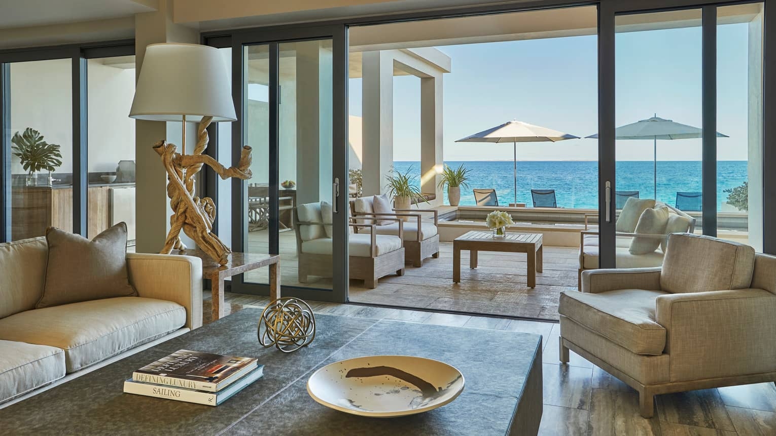 View from inside to indoor-outdoor living rooms with sofas, chairs, patio umbrellas and ocean in background