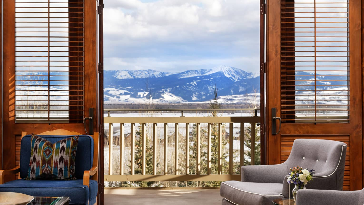 Plush chairs in a room with a wooden balcony overlooking the mountain peaks
