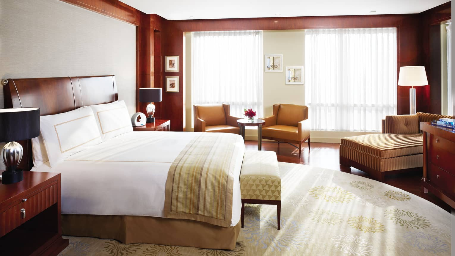Presidential Suite bed, striped blanket, bench, brown leather armchairs and chaise by window