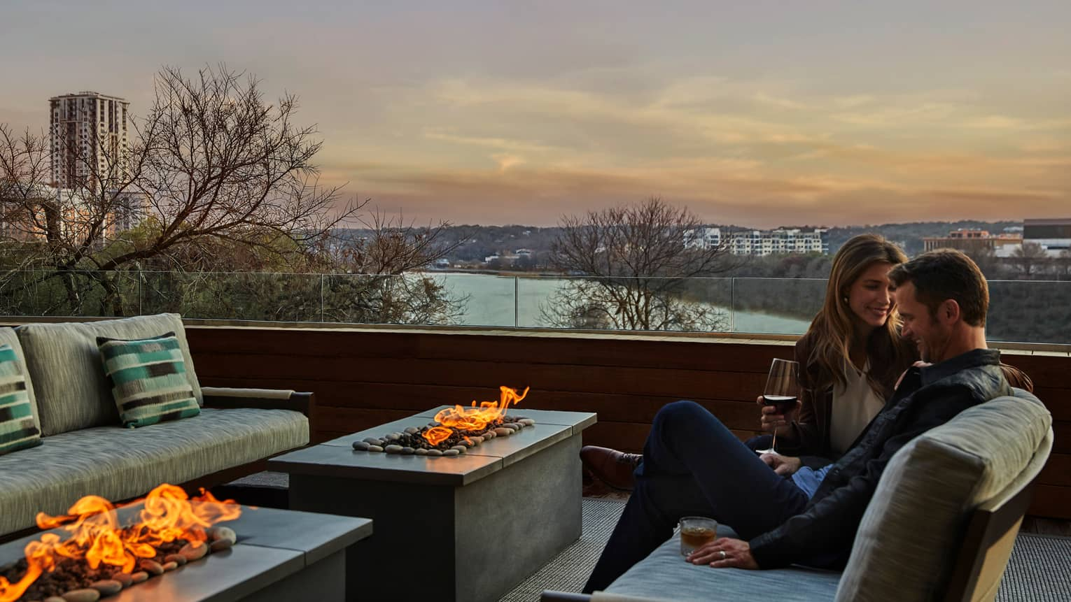 Couple sips wine in front of modern outdoor fireplace on Congressional Suite patio