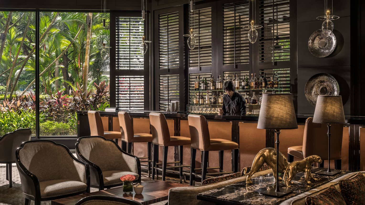 Bartender behind bar next to wood shutters, floor-to-ceiling windows, dining room
