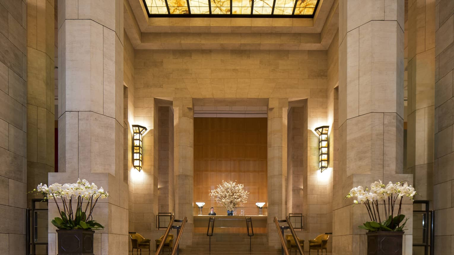 Tall marble columns, steps to hotel reception under amber skylight
