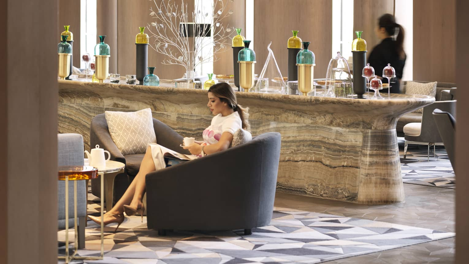 Woman drinks tea in large armchair by marble buffet bar