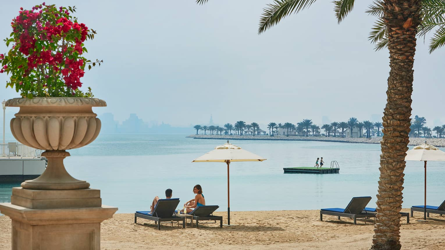 Couple on lounge chairs on golden sand beach past flower pot, children jump from platform in lagoon
