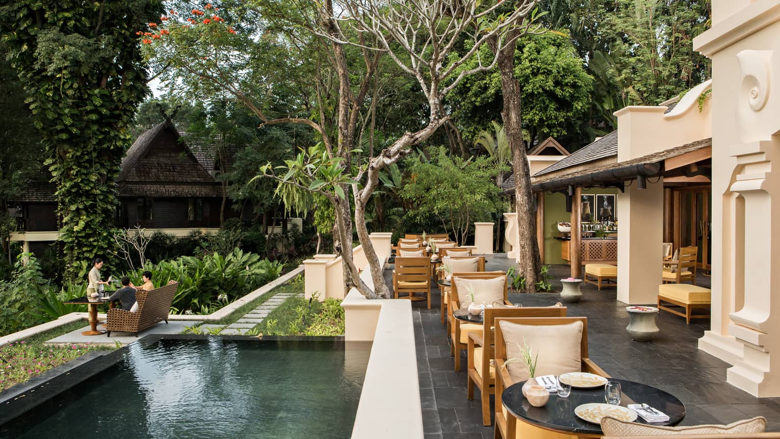 KHAO slate patio under shade of trees, long fountain by dining tables near large white columns