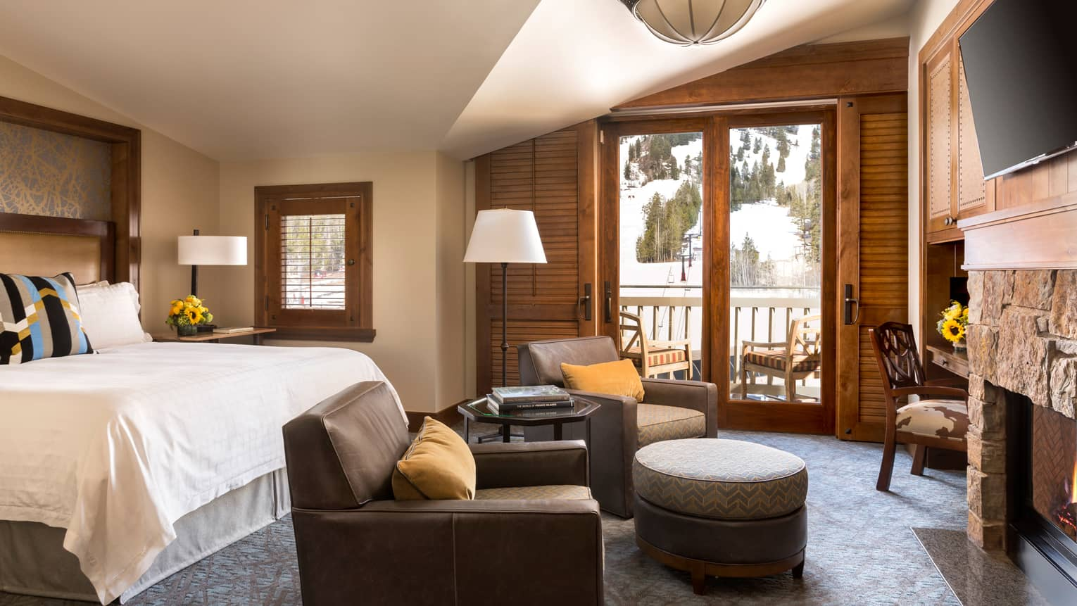 Mountain-View Room bed, large brown leather armchairs facing rustic stone fireplace
