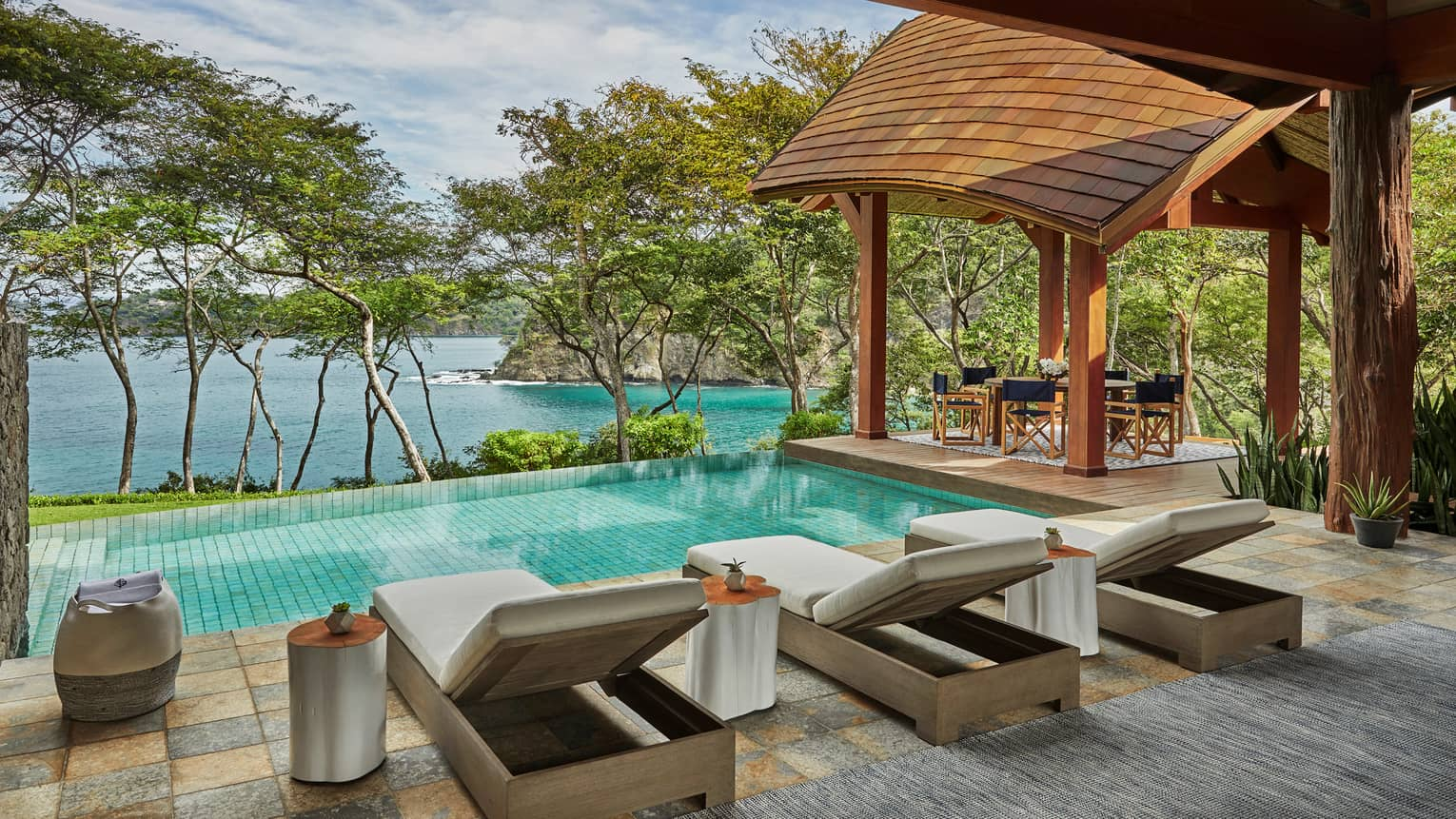 Miramar Suite patio tile patio, three long lounge chairs in front of plunge pool, row of trees, overlooking ocean