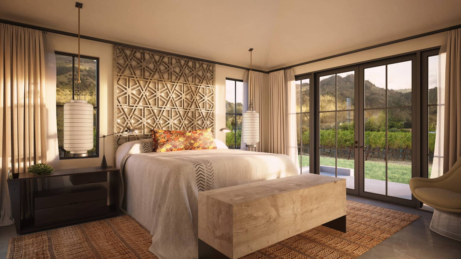 Hotel room bed with decorative headboard, wood bench by glass French doors to patio