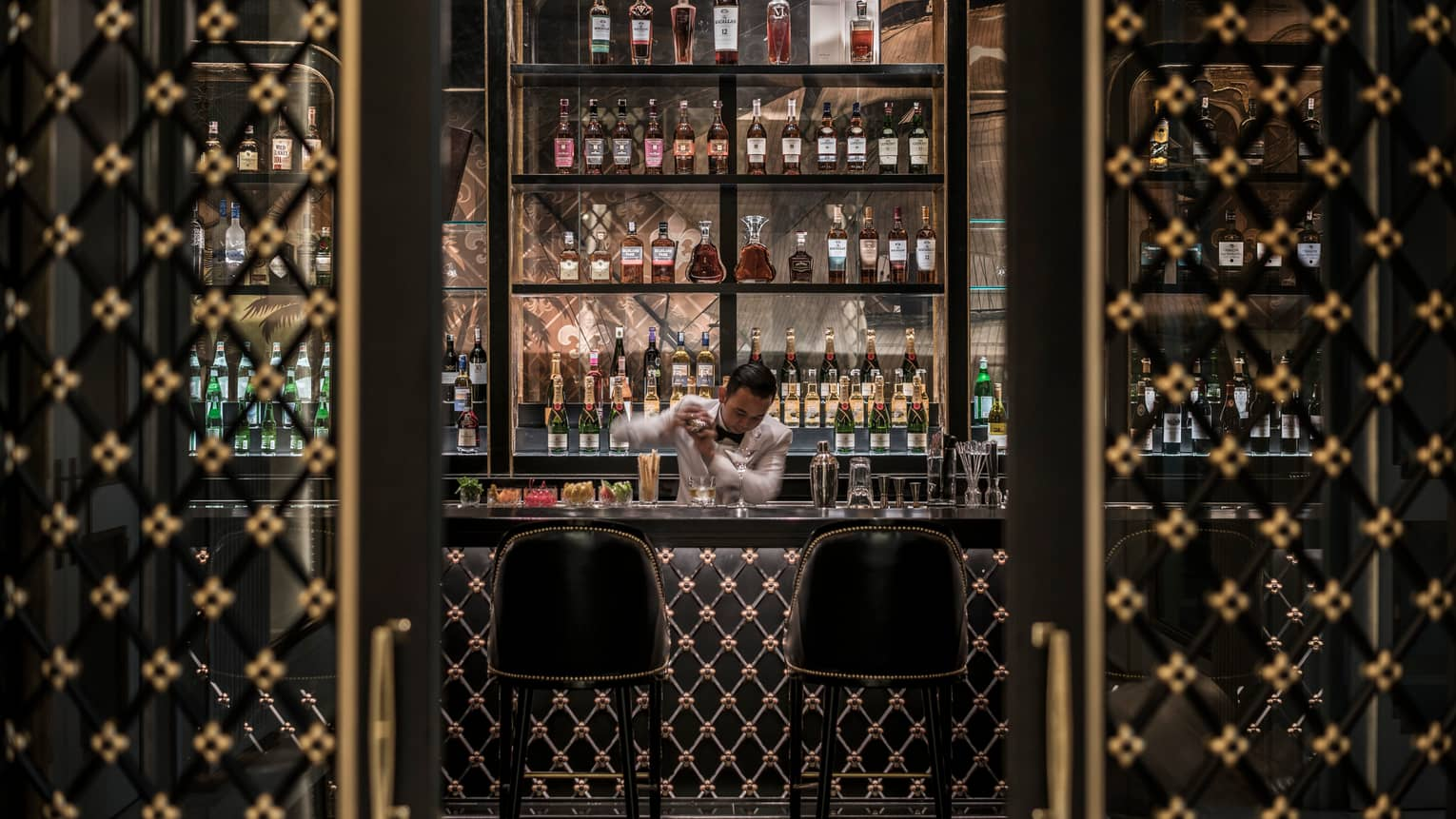 Bartender shakes drink behind dark Nautilus Bar with black-and-gold Art Deco-style design