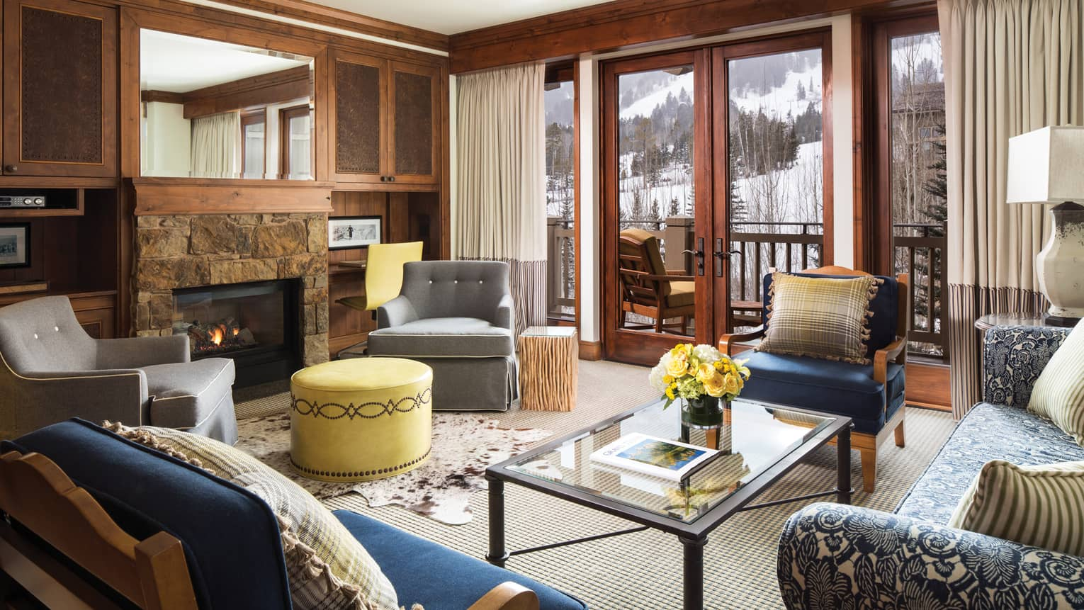 Valley View Resort Residence living room with grey and blue chairs, yellow ottomans, stone fireplace