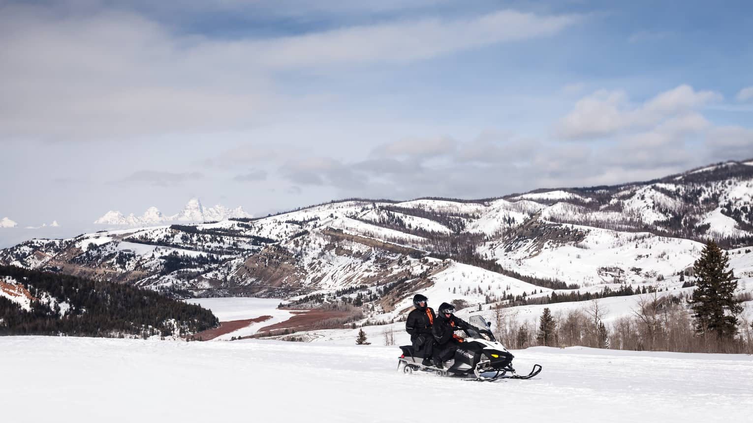 Aerial view of two people riding on a snowmobile in front of snowy mountains