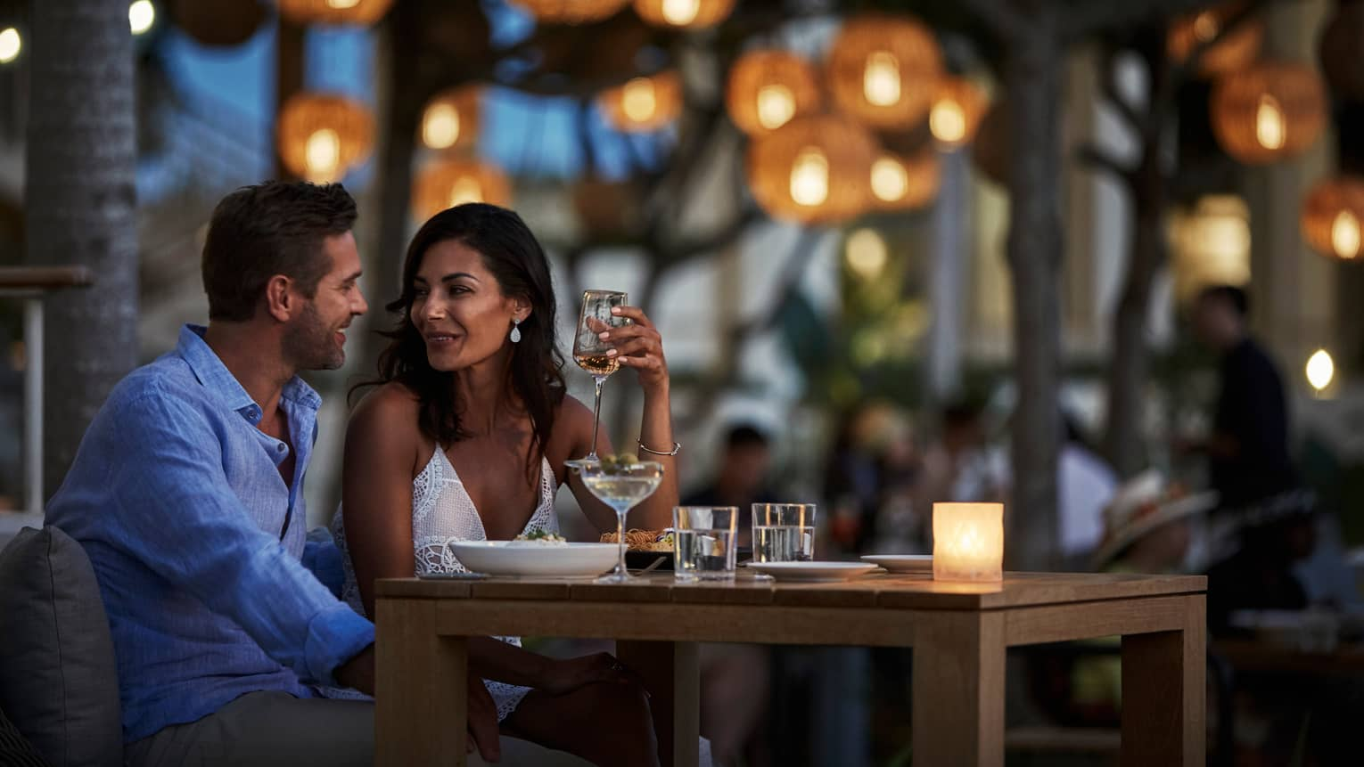 Man and woman with wine glass sit close at Noe patio dining table, lanterns
