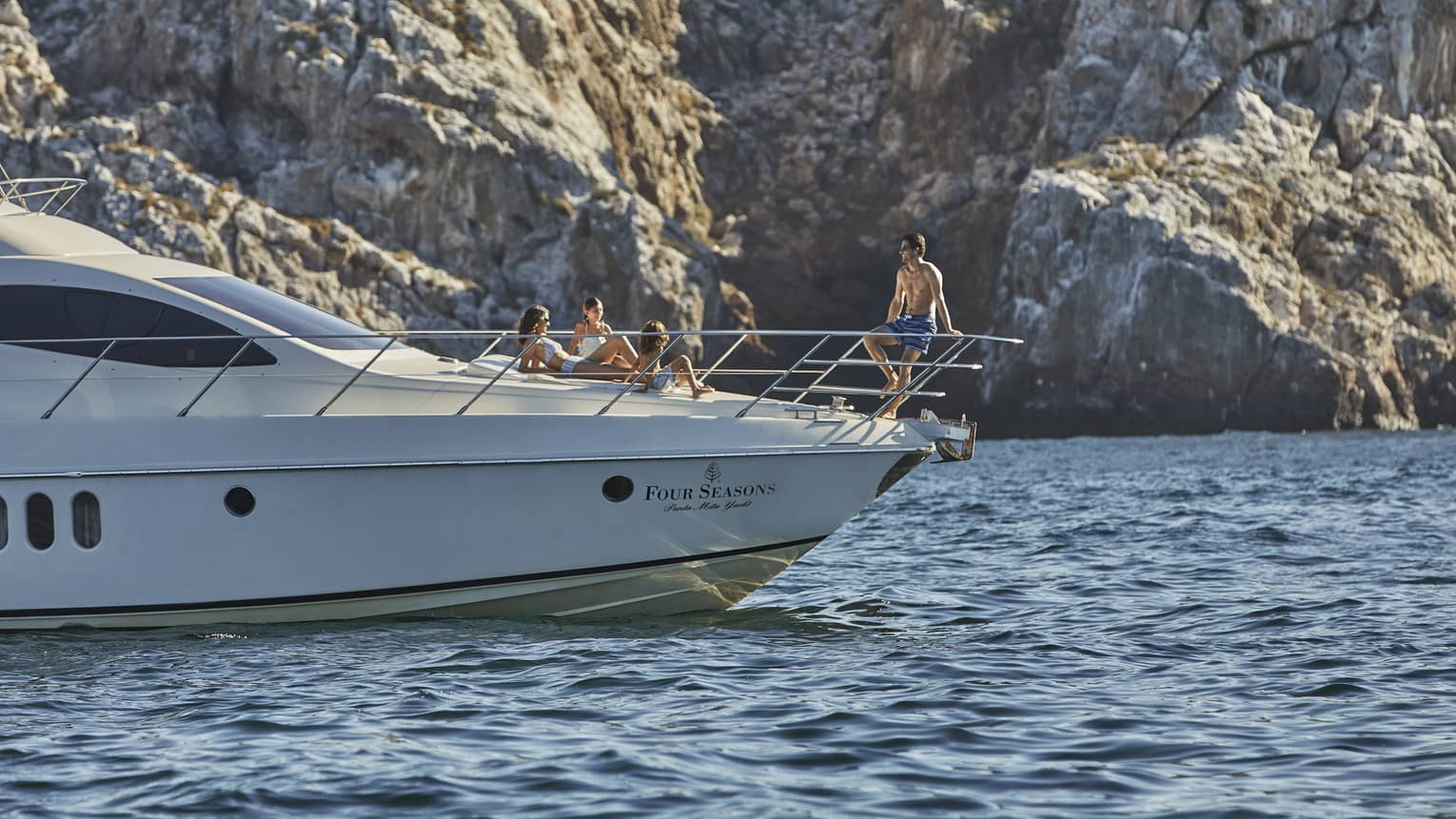 People relax on front of yacht sailing below large rocky cliff