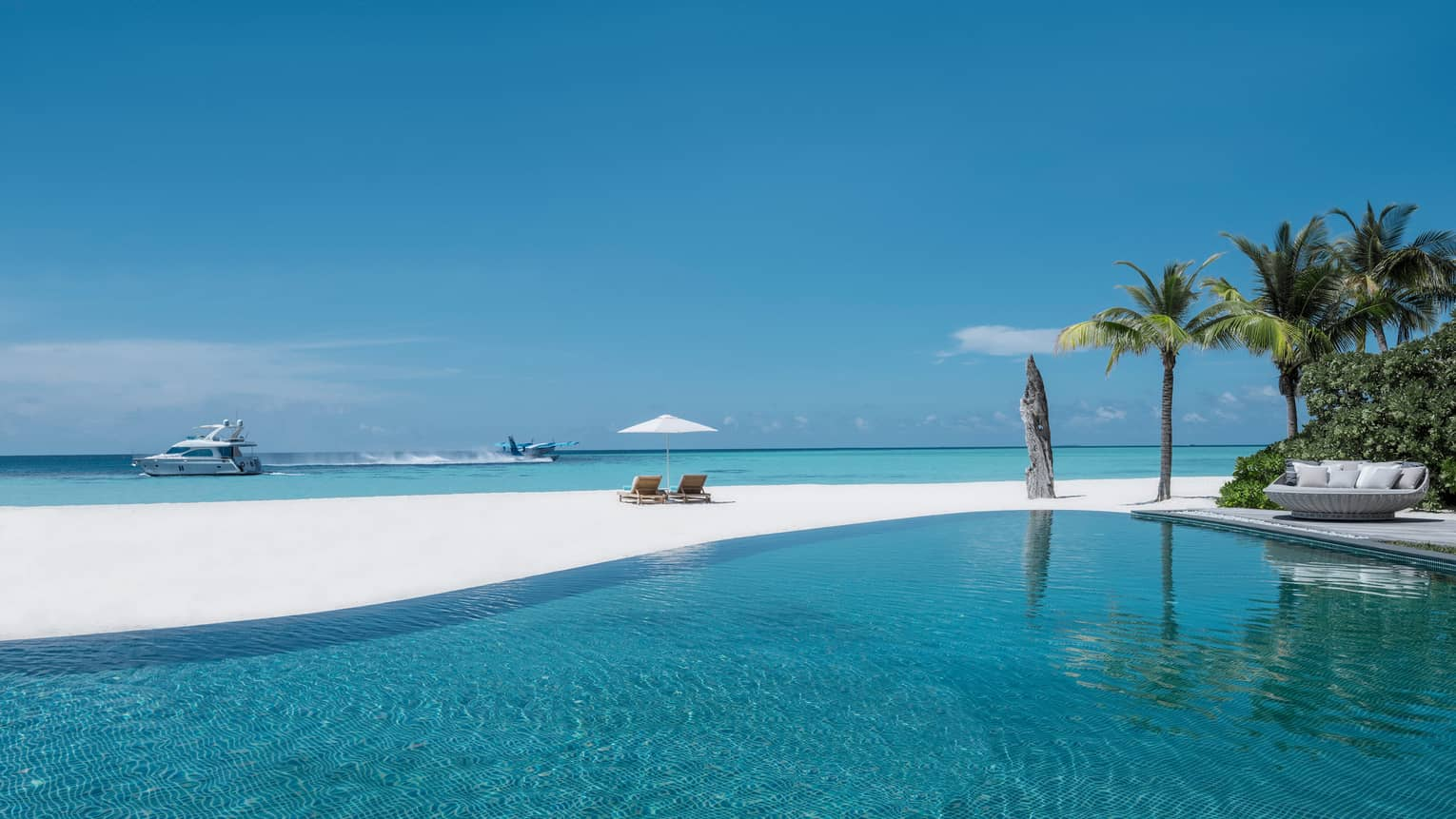 Infinity swimming pool by white sand beach, plane and catamaran boat in lagoon