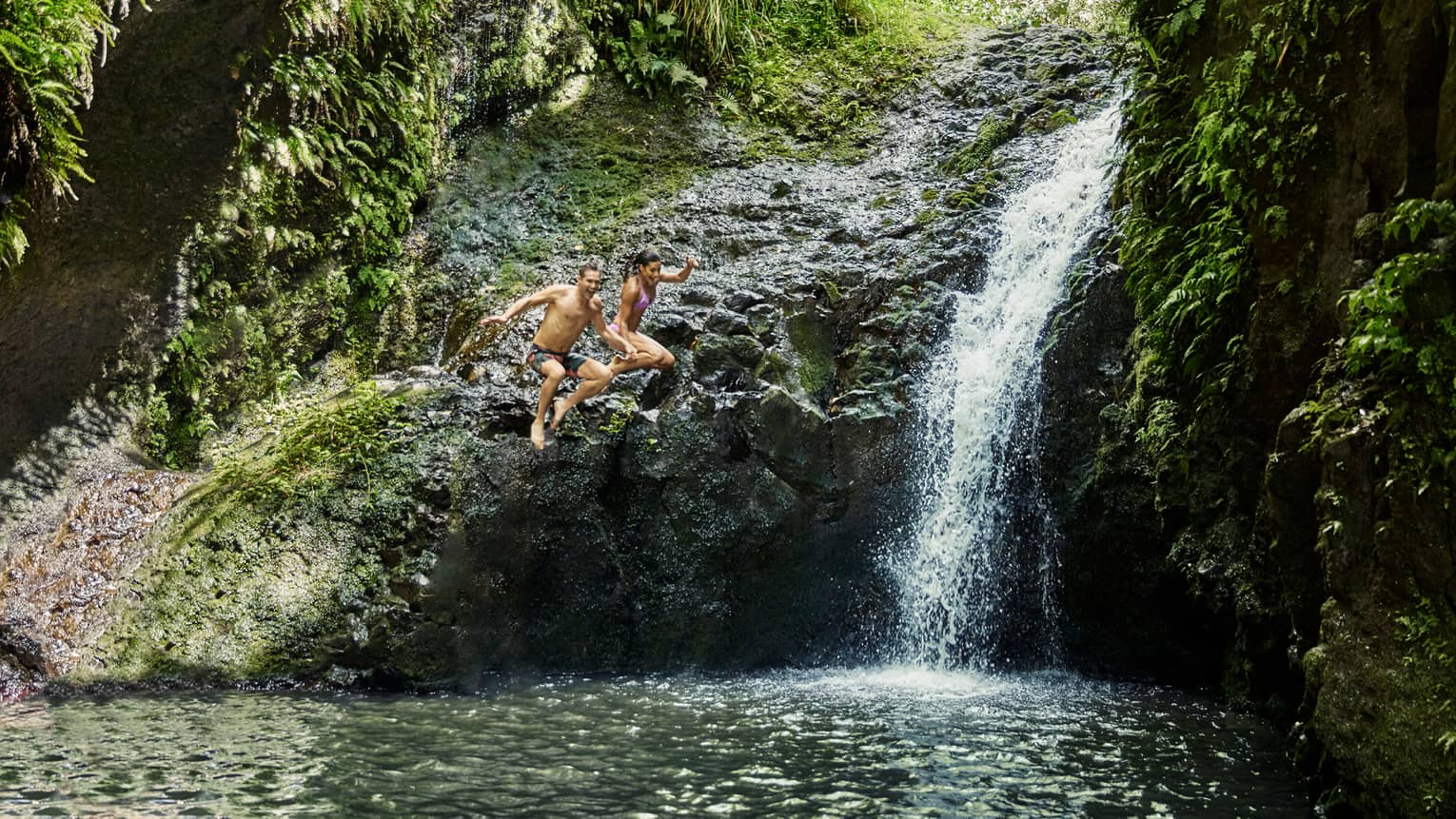 Man and woman laugh, hold hands as they jump from rocks next to waterfall