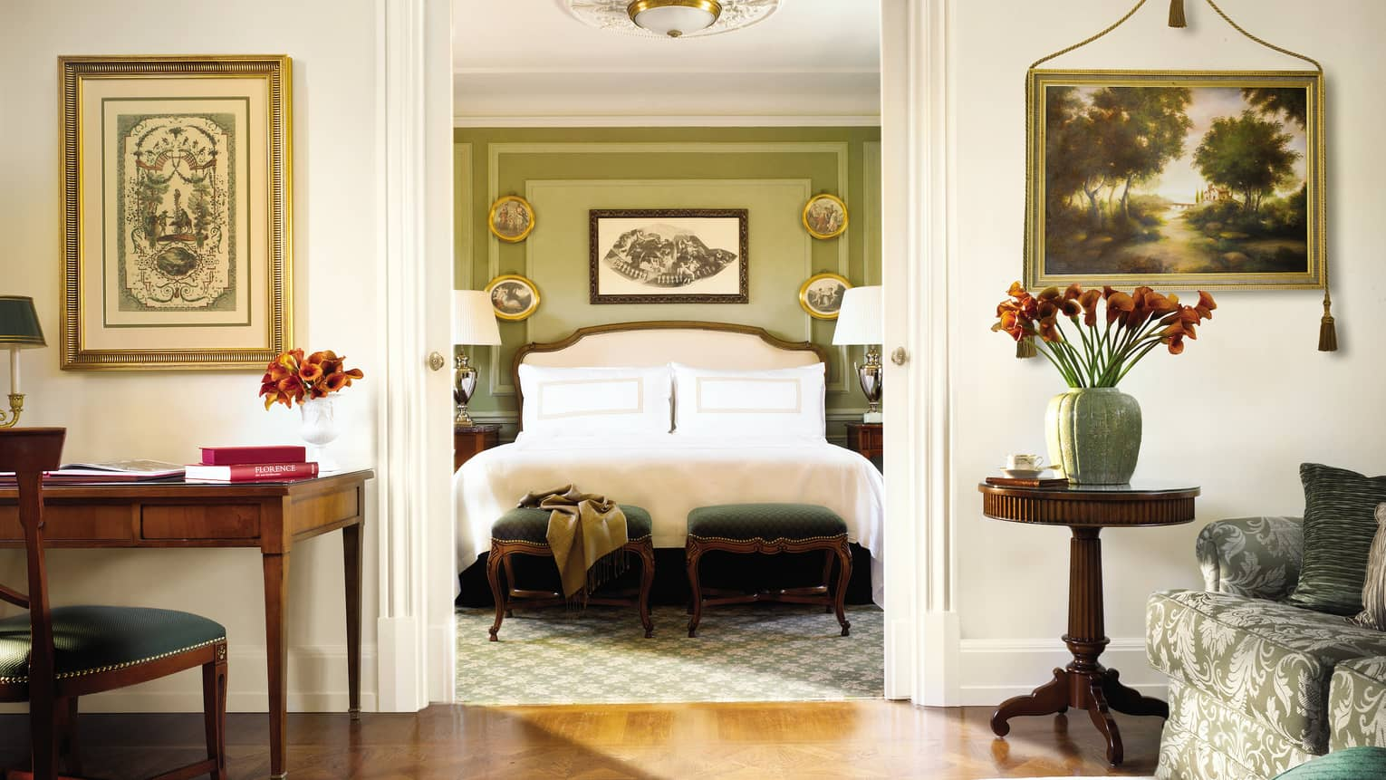 Four Seasons Executive Suite desk, chair by bedroom doorway, bed and scarf across green footstools