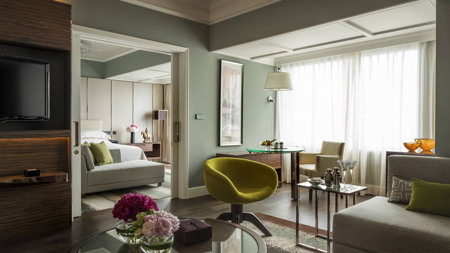 Executive Suite living area with modern green chair, table with flowers, green wall, bedroom door