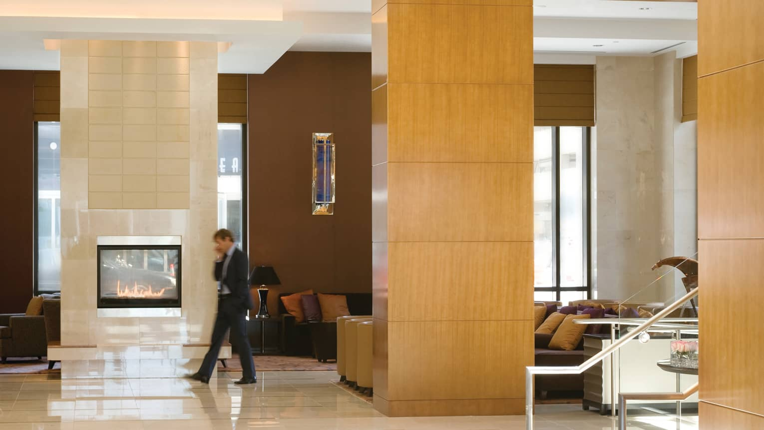 Man wearing suit walks by modern gas fireplace in Four Seasons Hotel Denver lobby