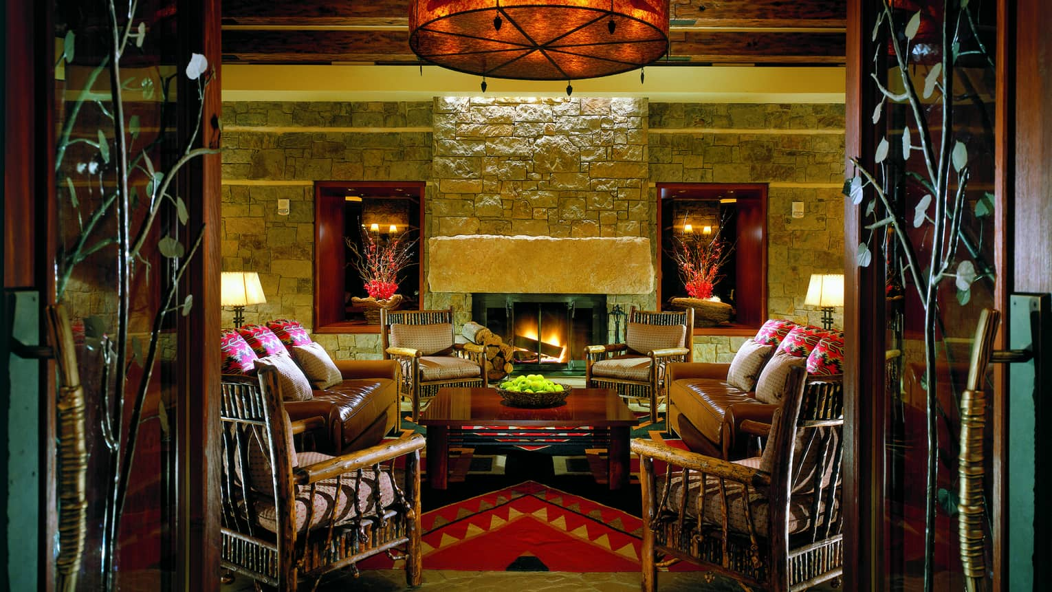 A dimly lit stone room with red accents, a circle of couches and chairs at the center