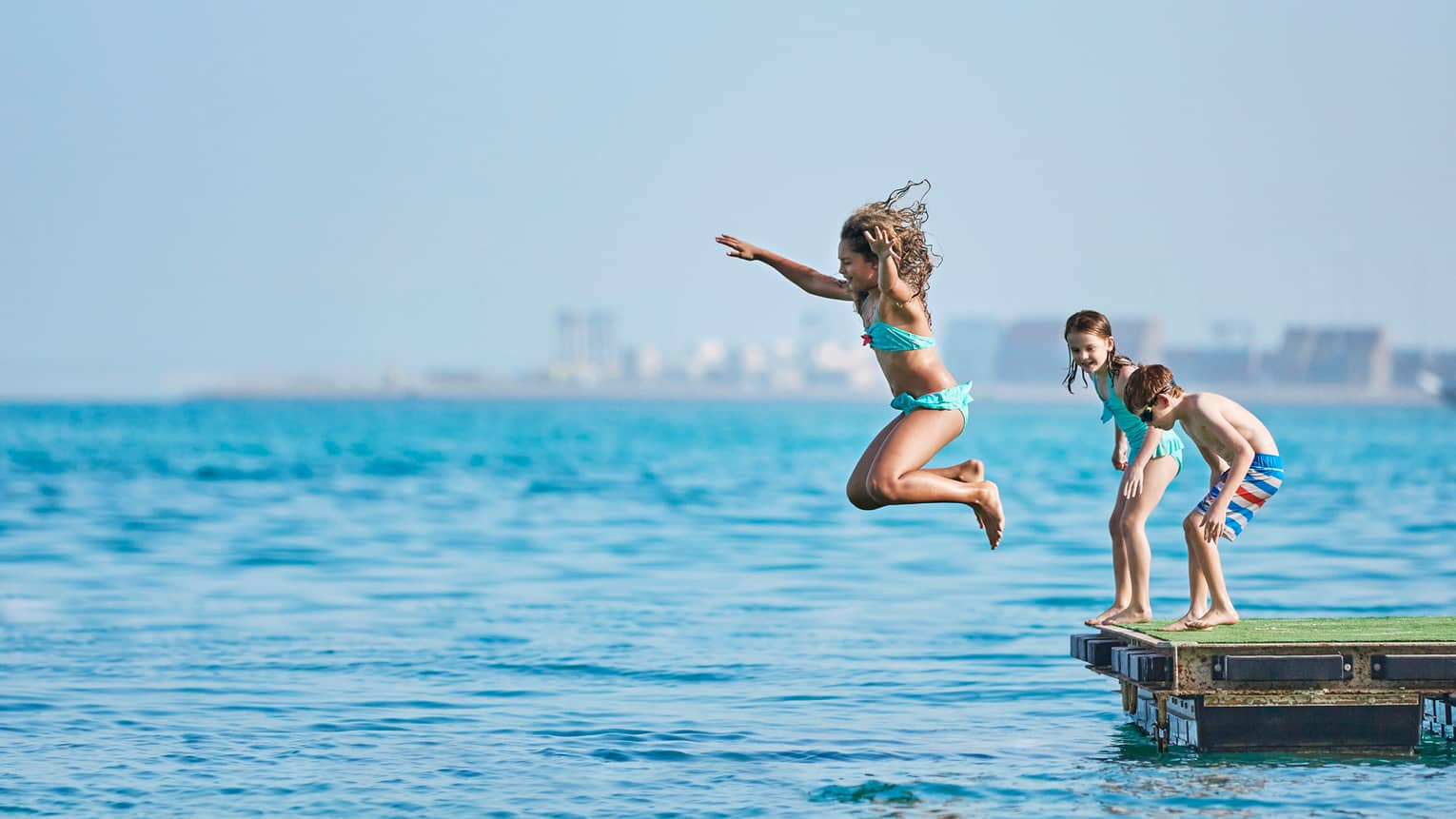 Little girl jumps into sea, two children stand behind her on wood platform