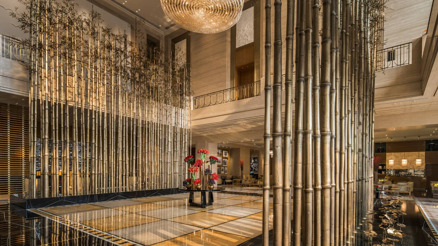 Tall bamboo sticks, leaves above Four Seasons Hotel Tianjin lobby, flowers, tile floor