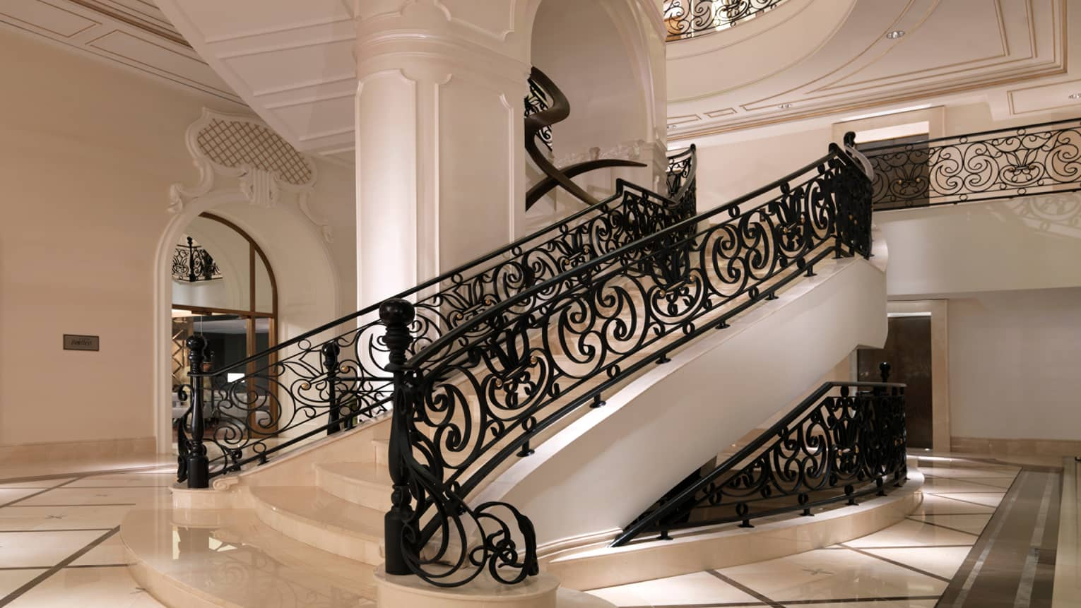 Hotel Beaux-Arts style white staircase with decorative black railings, white pillar, white tile floor