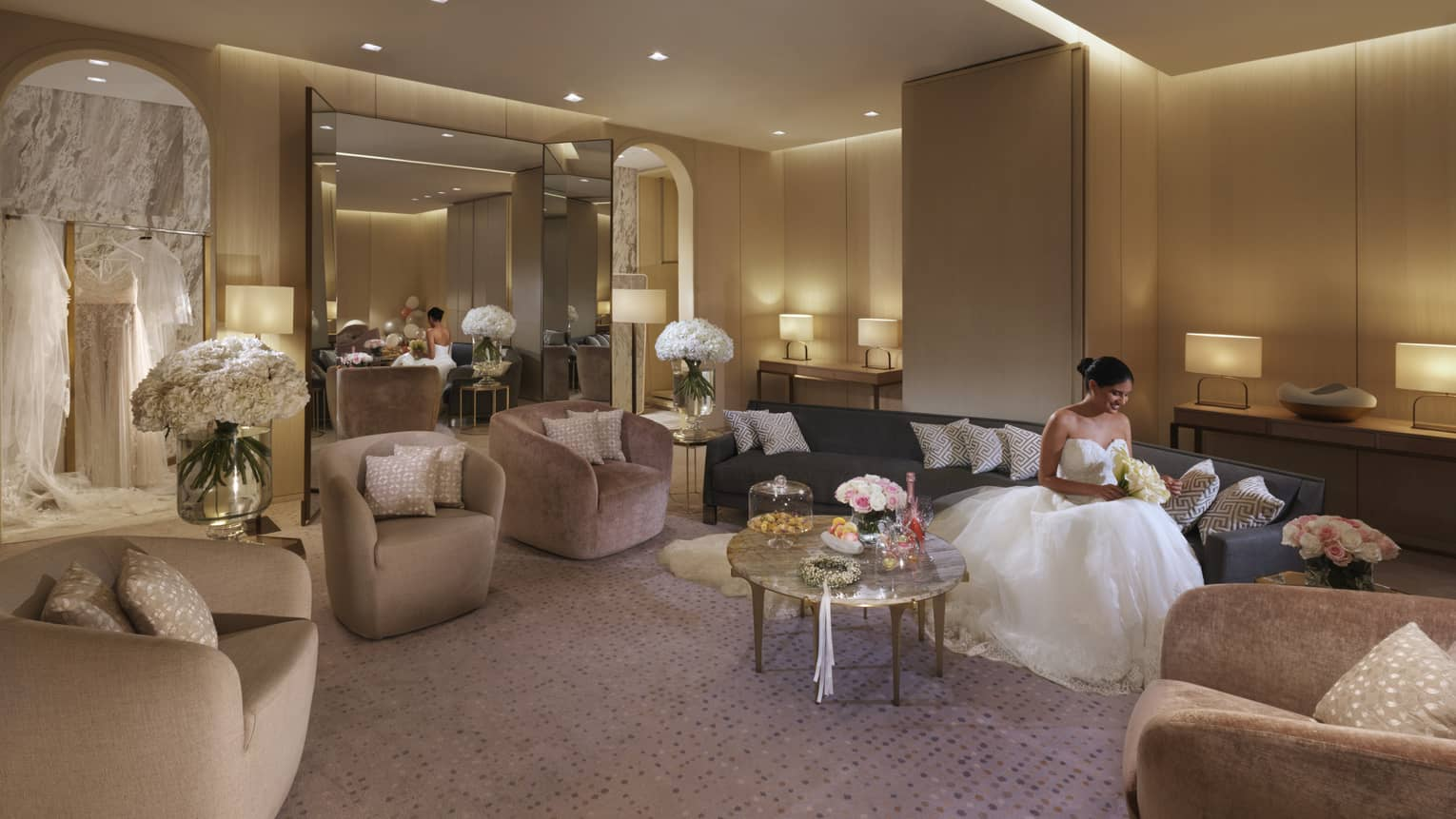 A bride dressed in her wedding dress, sits on a dark couch and reads a note in the bridal suite