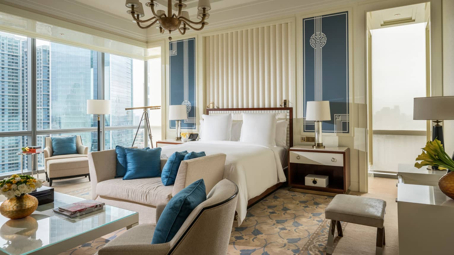 Chairman Suite large bed, plush sofas with blue cushions, corner windows with city views