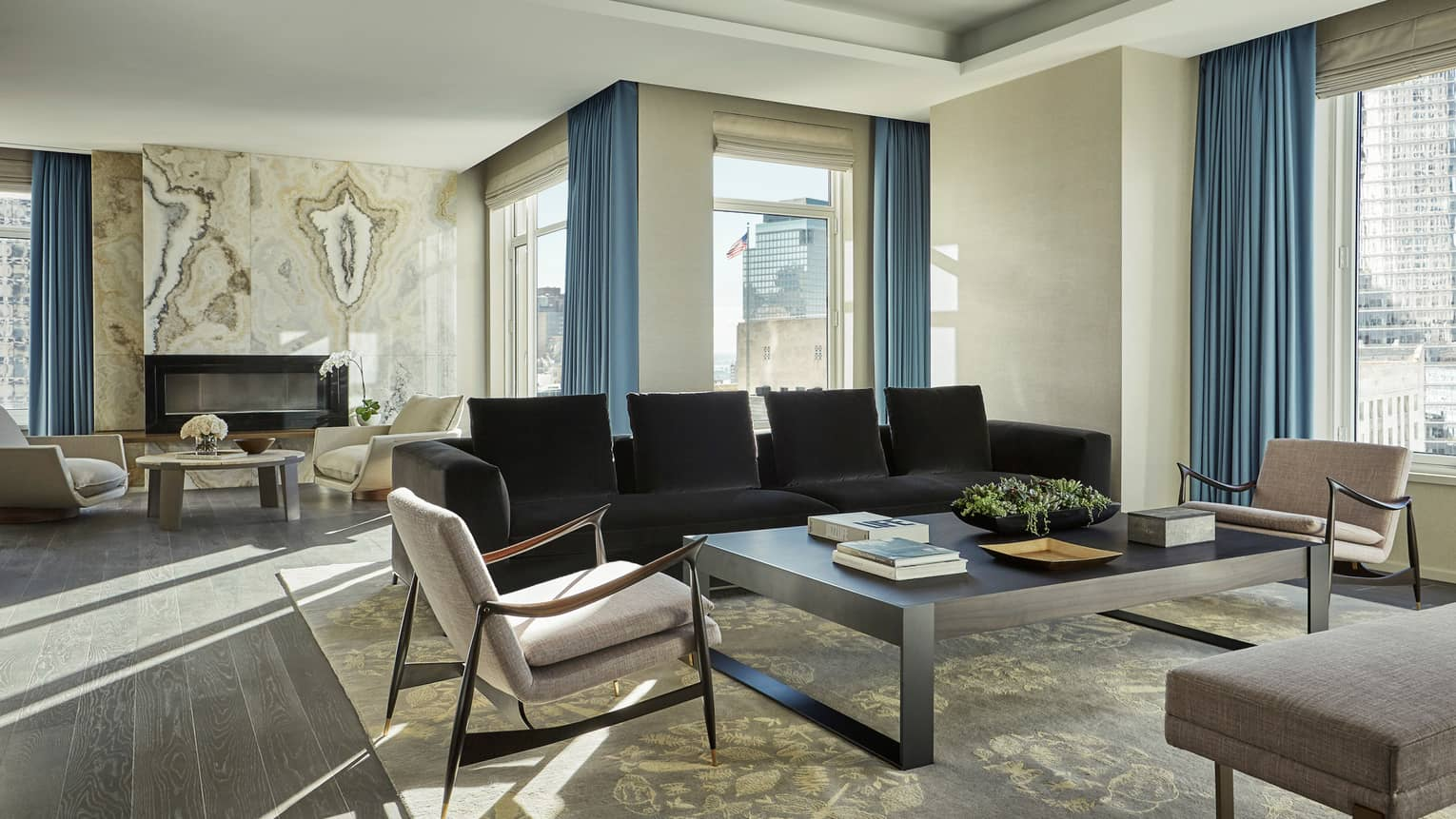 Royal Suite modern mid-century style armchairs, long black sofa, stonecut tile wall, windows