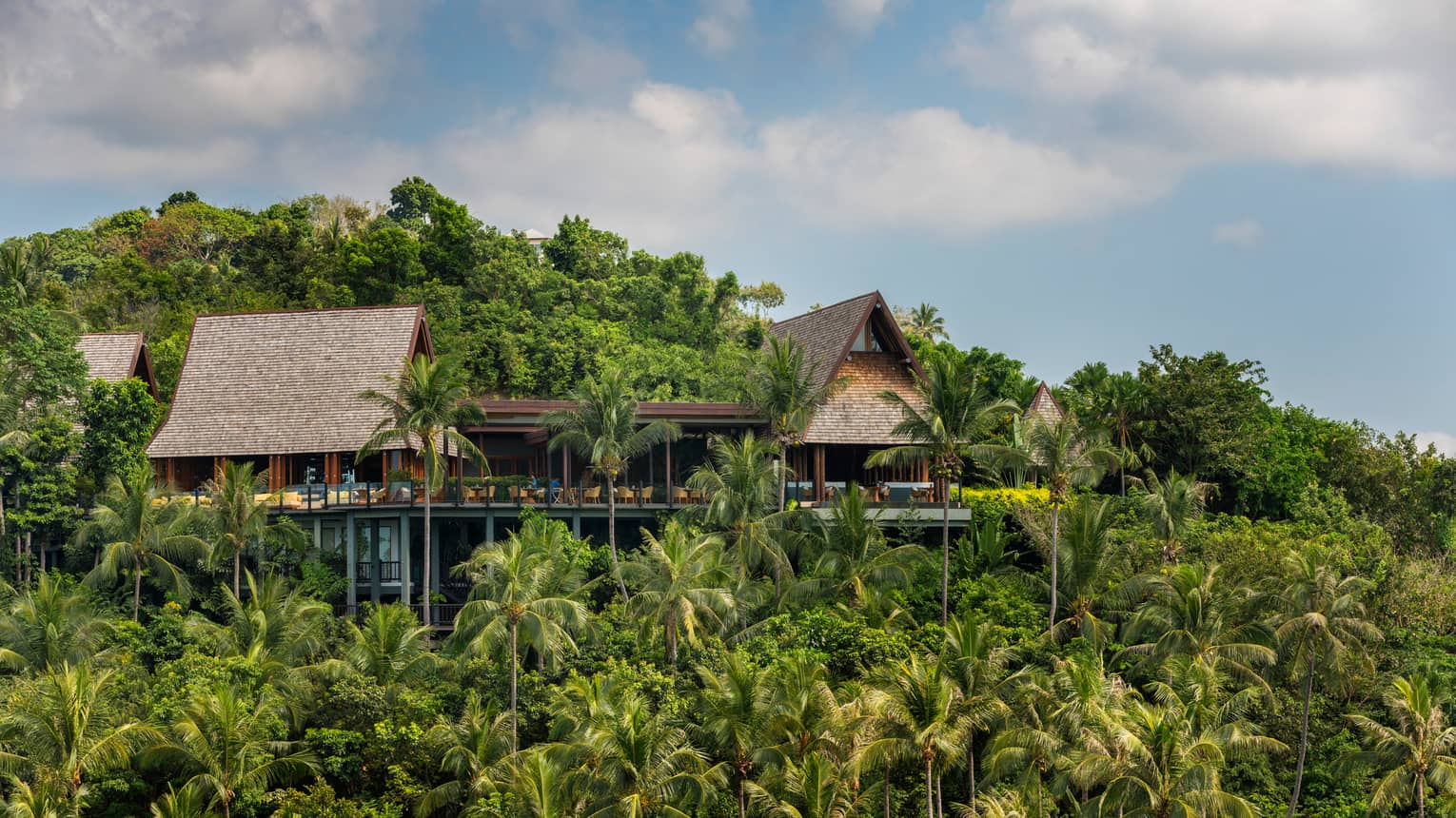 Exterior view of KOH Thai Kitchen and Bar building, perched on mountain amid tropical trees