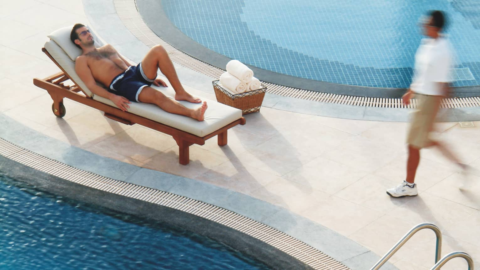 Man in swimsuit relaxes on beach lounge chair by swimming pool