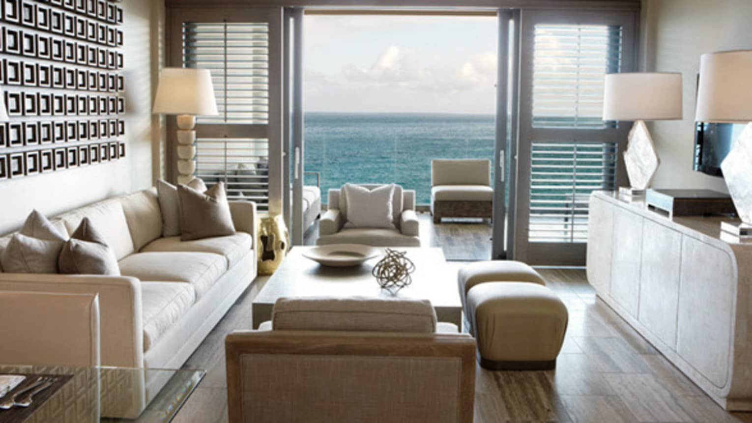 One-Bedroom Ocean-View Suite living room with white sofa and armchairs, patio door with ocean view