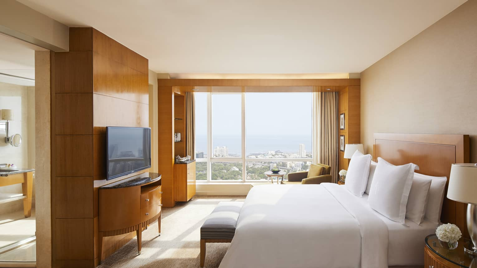 Deluxe room with natural light coming in and a view of the Mumbai skyline