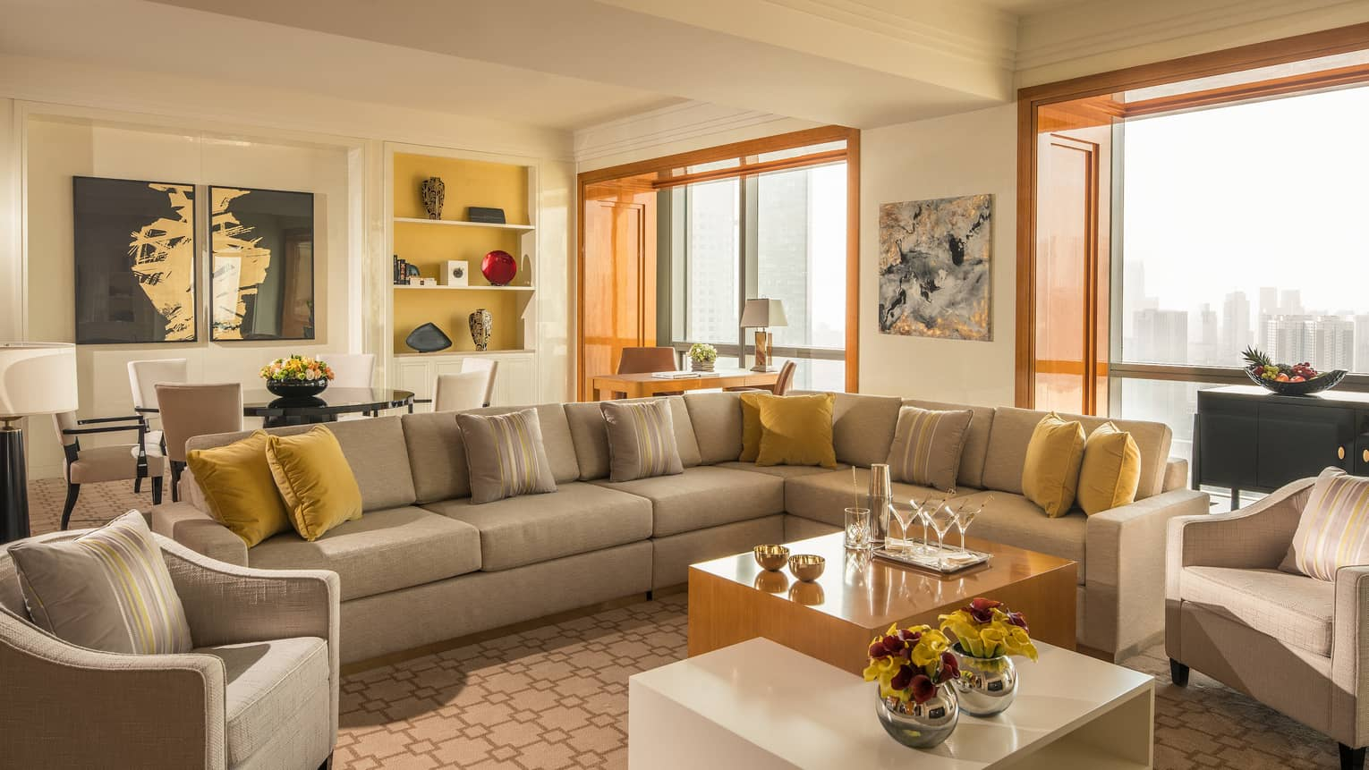 Four Seasons Suite long sofa sectional with yellow pillows, tables, large picture windows