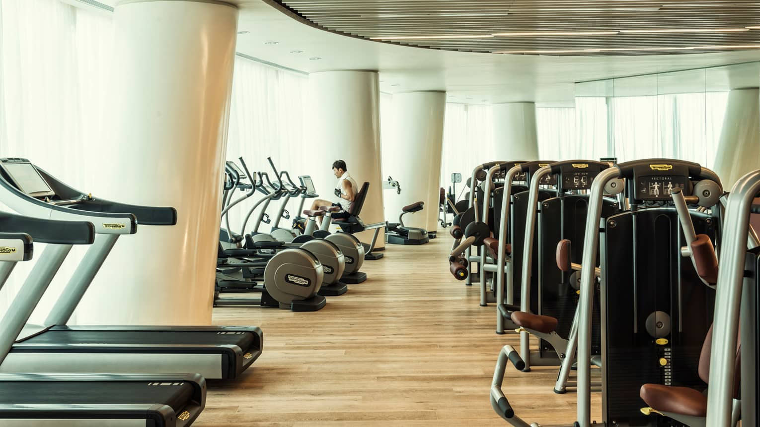 Cardio machines in bright fitness room with modern white pillars, man on bicycle machine